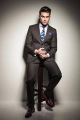 elegant business man sitting on a stool, thinking.