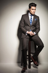 business man sitting on a stool while looking down thinking.
