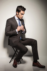 business man sitting on a stool while fixing his jacket