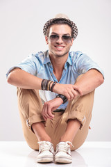 Young casual man sitting on studio background