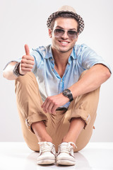 Smiling young man showing the thumbs up gesture