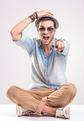 Young fashion man screaming while sitting