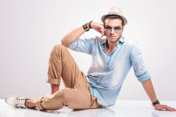 Young casual man sitting on the floor