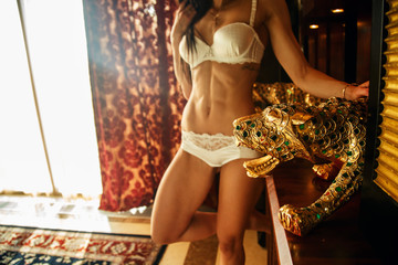 Charming fit girl with sexy body and golden lizard