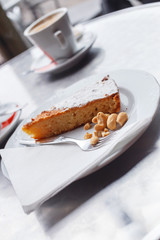 Cake with nuts on white plate.