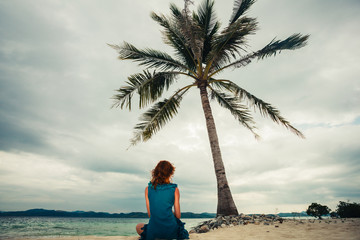 Woman sitting under palm tree on beach
