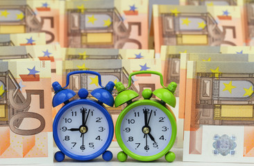 Miniature clocks showing nine and five o'clock with banknotes