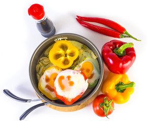 fried eggs on peppers placed on pan