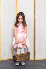 Little girl in a pink dress with white shoes holding brown