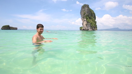 young guy stands in transparent azure sea water with swimming sm