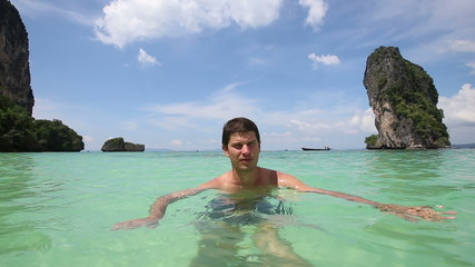 handsome guy stands in transparent azure sea water and speaks at