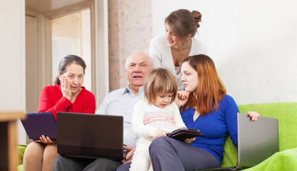 Happy family of with various portable computers