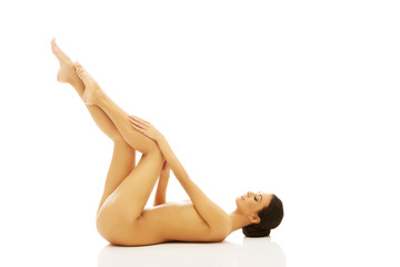 Nude woman lying on the floor with legs up