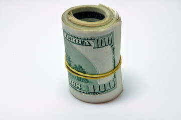 Roll of U.S. banknotes rolled up on white background