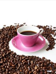 Tazzina di caffè rosa dentro curva di chicchi caffé