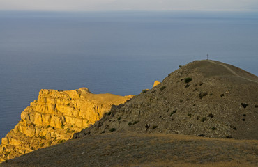 Coastal cliffs, lit by the morning sun. Crimea, Cape Meganom.