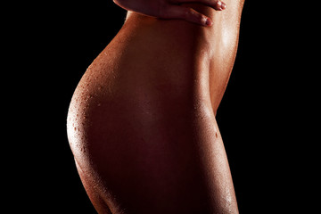 Side view naked female buttocks on dark background