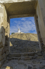A look at the lighthouse from the window of a ruined house