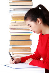 Side view woman sitting with stack of books