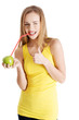 Woman in yellow top is drinking from and apple