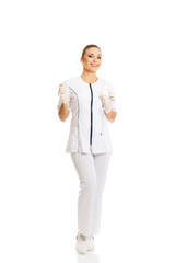 Full length female nurse holding a drip