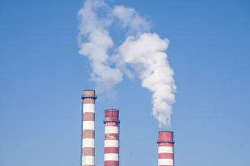 Smoking chimneys of thermal power plant on clear blue sky