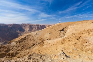 Group of people ascending desert mountain slope.