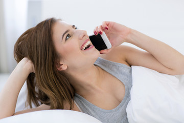 Smiling woman lying on the bed and talking smartphone