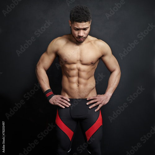 Athletic man on black wall background