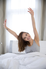 Happy young woman stretching on the bed