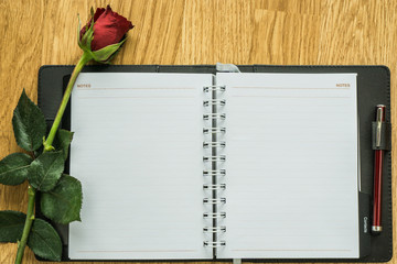 Blank paper and rose on wooden