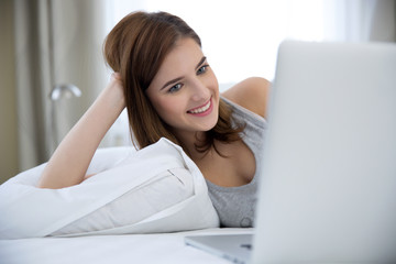Happy woman lying on the bed with laptop at home