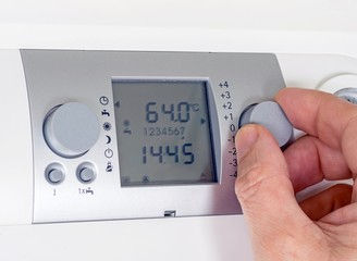 Adjusting the thermostat settings of a household heating system