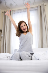 Portrait of a happy woman with raised hads up on the bed