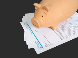 UK blank tax return form with piggy bank money box. Taxation.