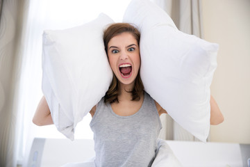 Angry young woman covering her ears with pillows