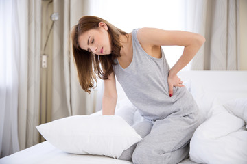 Young woman sitting on the bed with back pain