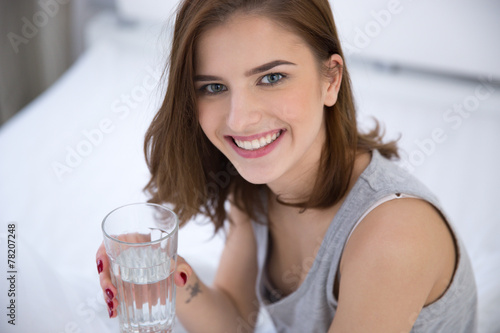 Portrait of a smiling woman holding glass of water Poster