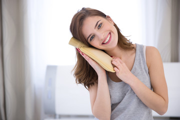 Portrait of a smiling young woman with a hot water bottle