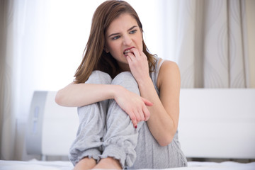 Worried young woman sitting on the bed at home