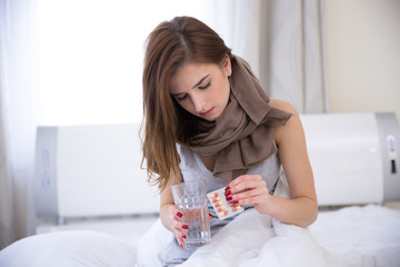 Young woman sitting on the bed with pills and glass of water