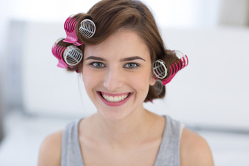 Portrait of a happy woman with curlers on her head