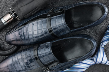 Classic blue men's shoes, tie, umbrella on the black leather