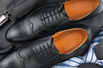 Classic men's shoes, tie, umbrella on the black leather