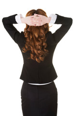 Young businesswoman with hands behind head.