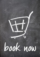 book now text and shopping cart sign on blackboard