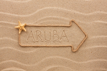 Arrow made of rope and sea shells with the word Aruba on the san