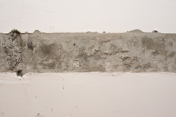 Plastered wall surface with strip of raw concrete