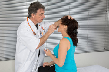Doctor checking throat of a nice woman