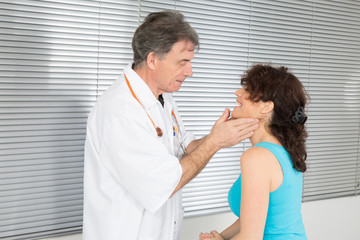 Male doctor touching the throat of a patient in the office